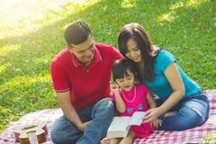Família que lê um livro junto na natureza fotografia de stock