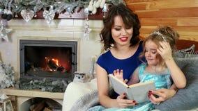 Família que lê uma história do Natal ao se sentar pela chaminé e pela árvore de Natal, a mãe e a filha leram um livro, nova filme