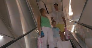 Família que monta para baixo na escada rolante no shopping vídeos de arquivo