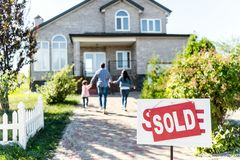 família que move-se na casa nova com quadro indicador vendido fotografia de stock
