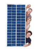 Família que olha através do painel solar Fotos de Stock