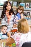 Família que olha o bibliotecário Showing Book imagem de stock