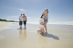 Família que olha o escudo na praia Imagem de Stock