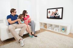 Família que olha o filme 3d na televisão Fotos de Stock Royalty Free