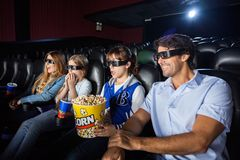 Família que olha o filme 3D no teatro do cinema Fotografia de Stock