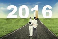 Família que olha o número 2016 na estrada Imagens de Stock