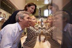 Família que olha produtos manufaturados no caso de vidro na viagem ao museu foto de stock royalty free