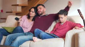 Família que olha a tevê e que usa a tabuleta digital em casa vídeos de arquivo