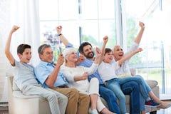 Família que olha a tevê no sofá imagem de stock royalty free