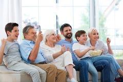 Família que olha a tevê no sofá imagem de stock