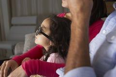 Família que olha a tevê vestir os vidros 3D e comer a pipoca Fotos de Stock Royalty Free