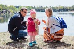 Família que passa o tempo junto perto do lago fora Foto de Stock