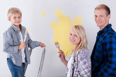 Família que pinta uma parede Fotos de Stock Royalty Free