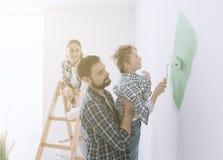 Família que pinta uma sala junto imagens de stock