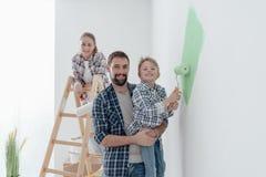 Família que pinta uma sala junto Imagem de Stock