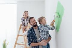 Família que pinta uma sala junto Fotos de Stock Royalty Free