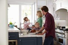 Família que prepara a refeição de Turquia do assado na cozinha junto imagens de stock