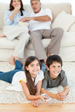 Família que presta atenção à tevê na sala de visitas Imagem de Stock Royalty Free