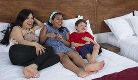 Família que reclina na cama na televisão fotos de stock
