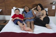 Família que reclina na cama na televisão fotos de stock royalty free