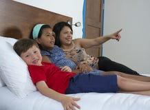 Família que reclina na cama na televisão foto de stock