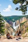 Família que relaxa e que aprecia a vista bonita da cachoeira em caminhar a viagem nas montanhas imagem de stock