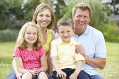 Família que relaxa no campo imagem de stock