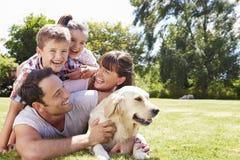 Família que relaxa no jardim com cão de estimação