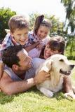 Família que relaxa no jardim com cão de estimação fotos de stock royalty free