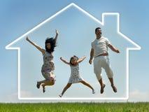 A família que salta com HOME nas nuvens Imagem de Stock Royalty Free