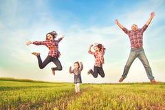 A família que salta no campo Imagem de Stock Royalty Free