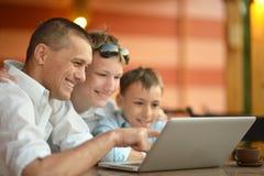Família que senta-se com portátil Foto de Stock