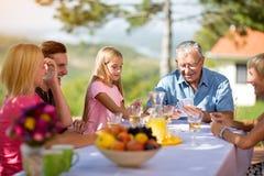 Família que senta-se em cartões de jogo da tabela Imagens de Stock