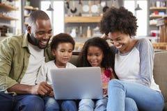 Família que senta-se em Sofa In Open Plan Lounge que usa o portátil foto de stock royalty free