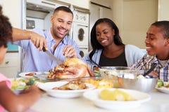Família que senta-se em torno da tabela em casa que come a refeição foto de stock royalty free