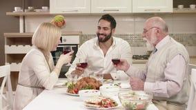 Família que senta-se em torno de uma tabela, comendo, comunicando e tendo o divertimento durante o jantar da família vídeos de arquivo