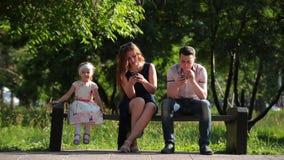 Família que senta-se em um banco com smartphones vídeos de arquivo
