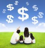 Família que senta-se em um prado com dinheiro das nuvens fotos de stock