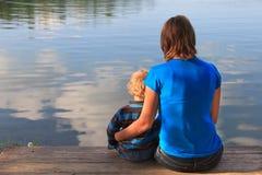 família que senta-se na doca de madeira Fotografia de Stock