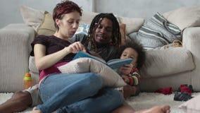 Família que senta-se na história da leitura do assoalho junto vídeos de arquivo