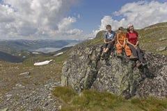 Família que senta-se na pedra grande Imagens de Stock Royalty Free