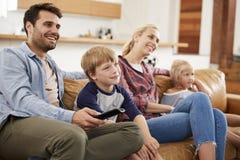 Família que senta-se na televisão de observação de Sofa In Open Plan Lounge fotografia de stock royalty free