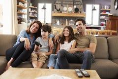 Família que senta-se na televisão de observação de Sofa In Open Plan Lounge foto de stock