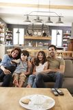 Família que senta-se na televisão de observação de Sofa In Open Plan Lounge imagem de stock