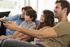 Família que senta-se na televisão de observação de Sofa In Open Plan Lounge imagens de stock