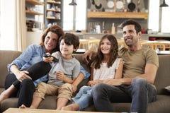 Família que senta-se na televisão de observação de Sofa In Open Plan Lounge fotos de stock royalty free