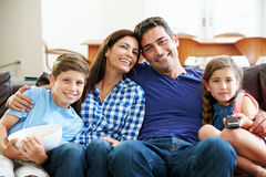 Família que senta-se na tevê de Sofa Watching junto Fotografia de Stock Royalty Free