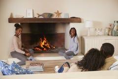 Família que senta-se no fogo aberto de Sofa In Lounge Next To imagens de stock royalty free