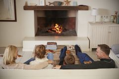 Família que senta-se no fogo aberto de Sofa In Lounge Next To fotografia de stock