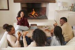 Família que senta-se no fogo aberto de Sofa In Lounge Next To que come a pizza fotografia de stock